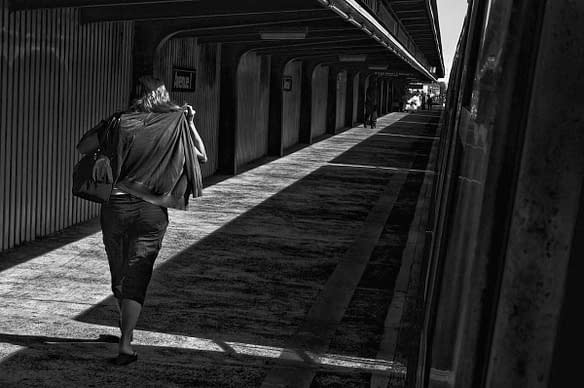 black and white photo of person walking along subway platform in Brooklyn, NY