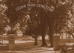 "The name ""Cedar Park Cemetery"" spans the arch of the entry gate to a cemetery. Large trees occupy the middle ground, and tombstones the background."