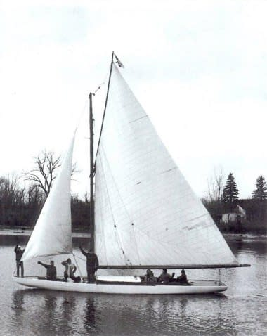 An old, black-and-white photo of a sloop on the river. It is manned by seven people.