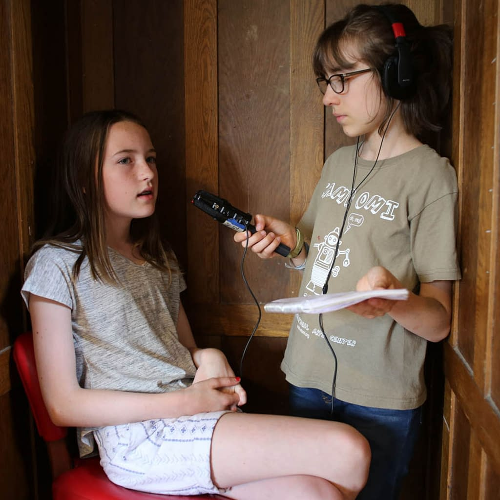 On teen girl wearing headphones hold a microphone, recording another teen girl.