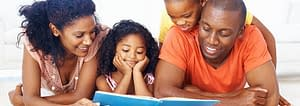 A mother, a father, a son, and a daughter all happily reading the same book together.