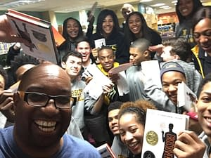Kwame Alexander poses with teens and his book The Crossover