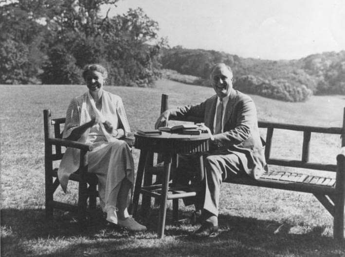A black and white photograph of Franklin and Eleanor Roosevelt sitting on wooden chairs in a field, smiling at the camera.