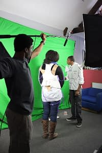 A teen holds a boom mic over two other teens in front of a green screen. The two wear costumes made out of paper.